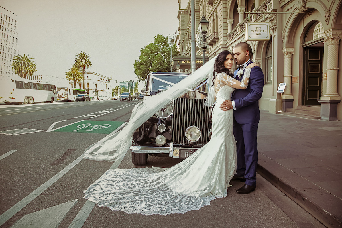 bride_and_groom_standing_outdoors_on_road_in_front_of_old_fashioned_black_car_dress_train_spread_out.jpg
