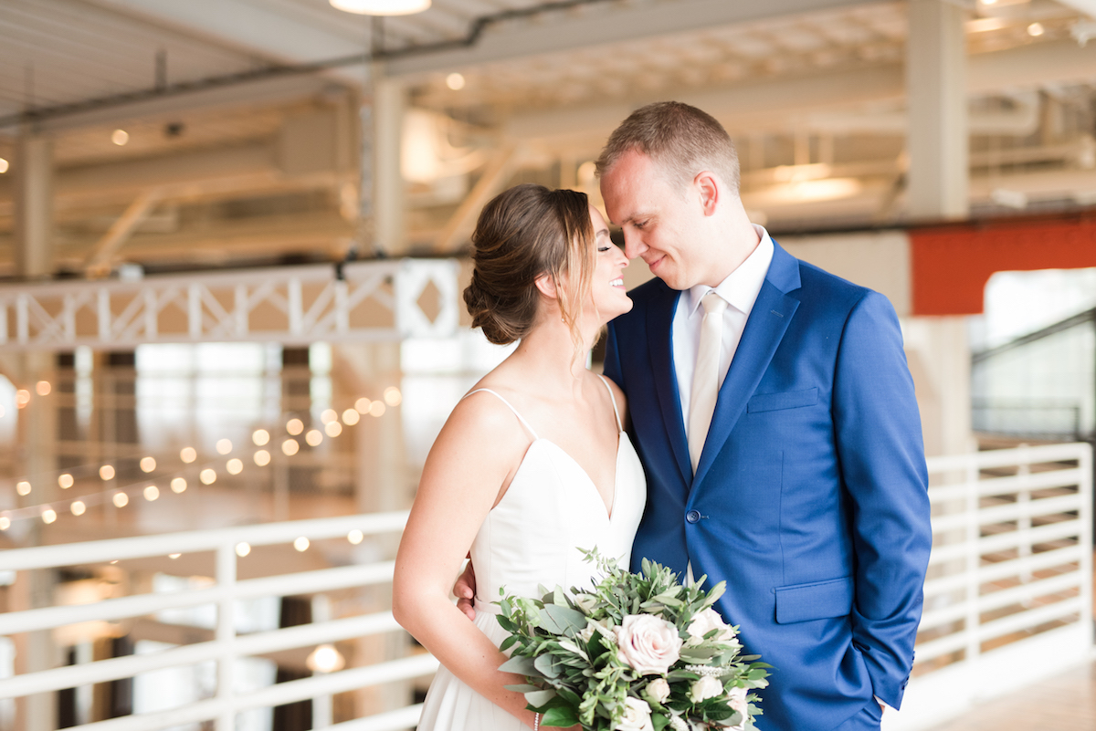 bride_and_groom_touching_noses_industrial_wedding_venue_string_lights_bouquet.jpg