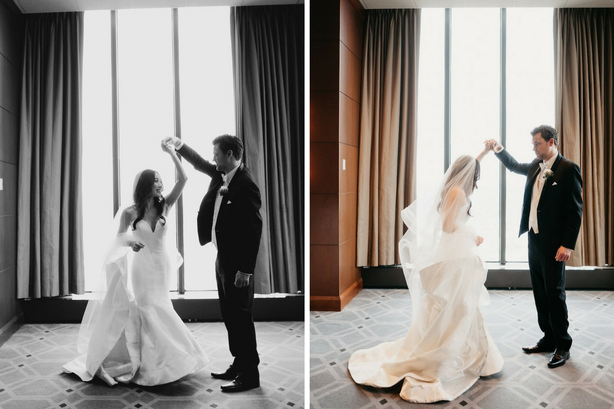 bride_and_groom_twirling_in_wedding_venue_large_windows_natural_light.jpg