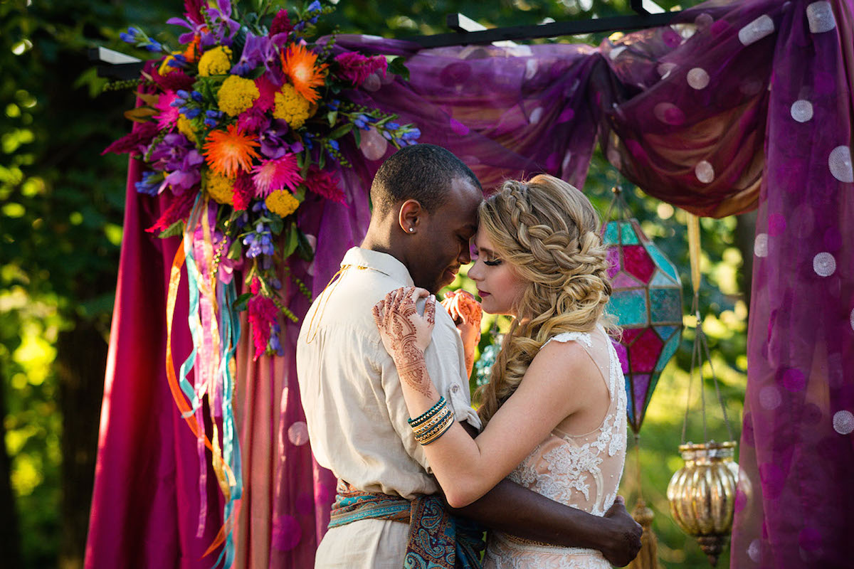 bride_and_groom_under_colorful_arch.jpg