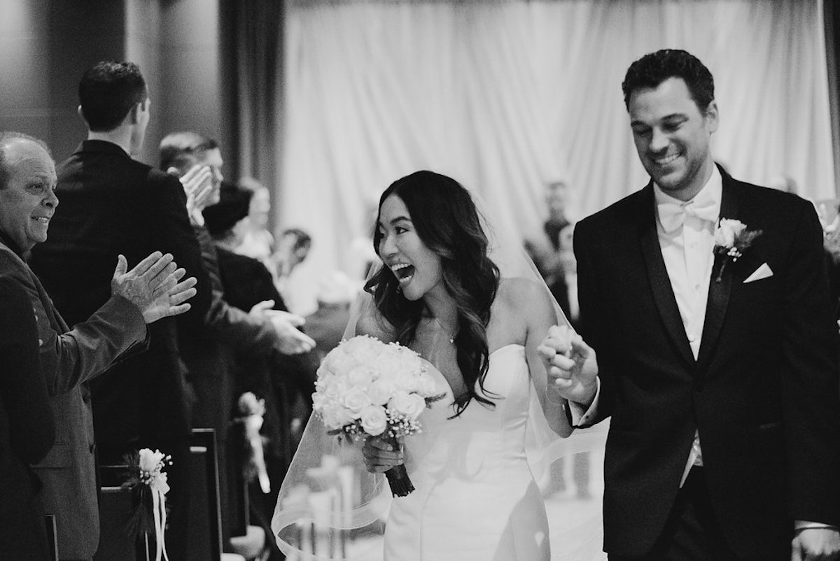 bride_and_groom_walking_down_aisle_black_and_white_smiling.jpg