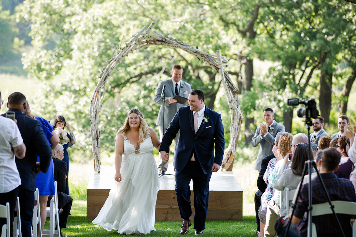 bride_and_groom_walking_down_aisle_together_smiling_outdoor_ceremony.jpg