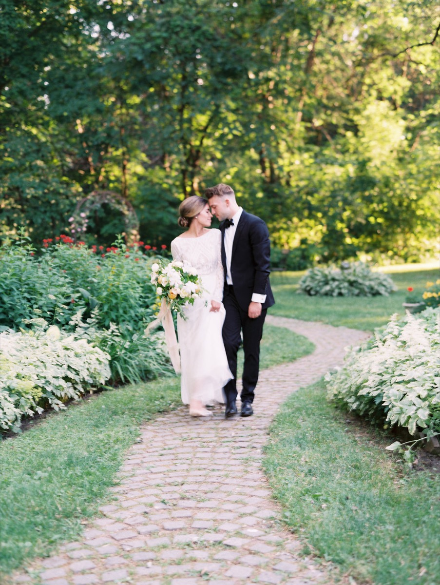 bride_and_groom_walking_on_cobblestone_path_touching_foreheads.jpg