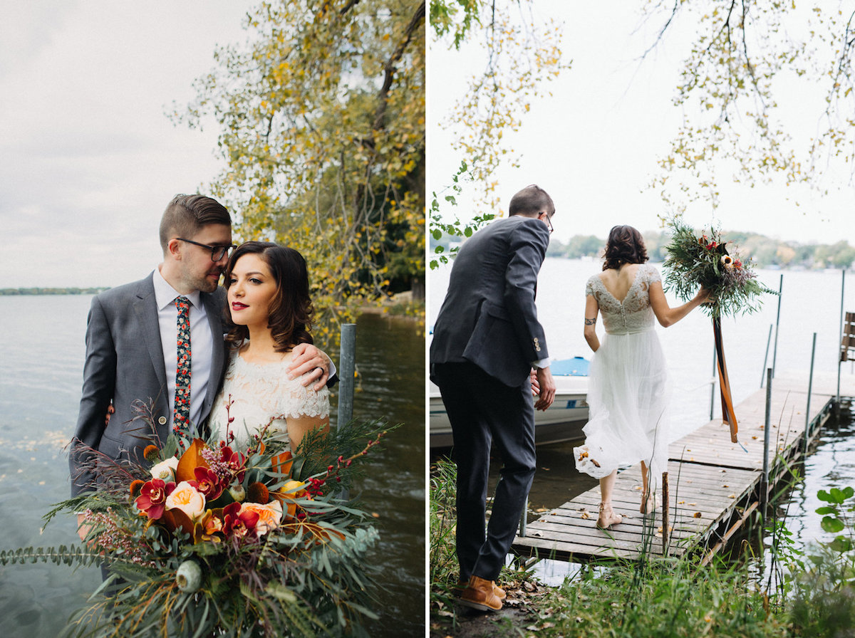 bride_and_groom_walking_on_lake_dock_holding_large_autumn_bouquet.jpg