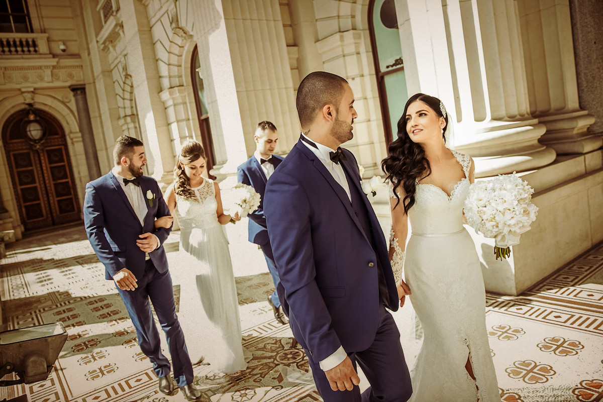 bride_and_groom_walking_outdside_of_fancy_stone_building_bridal_party_in_background.jpg