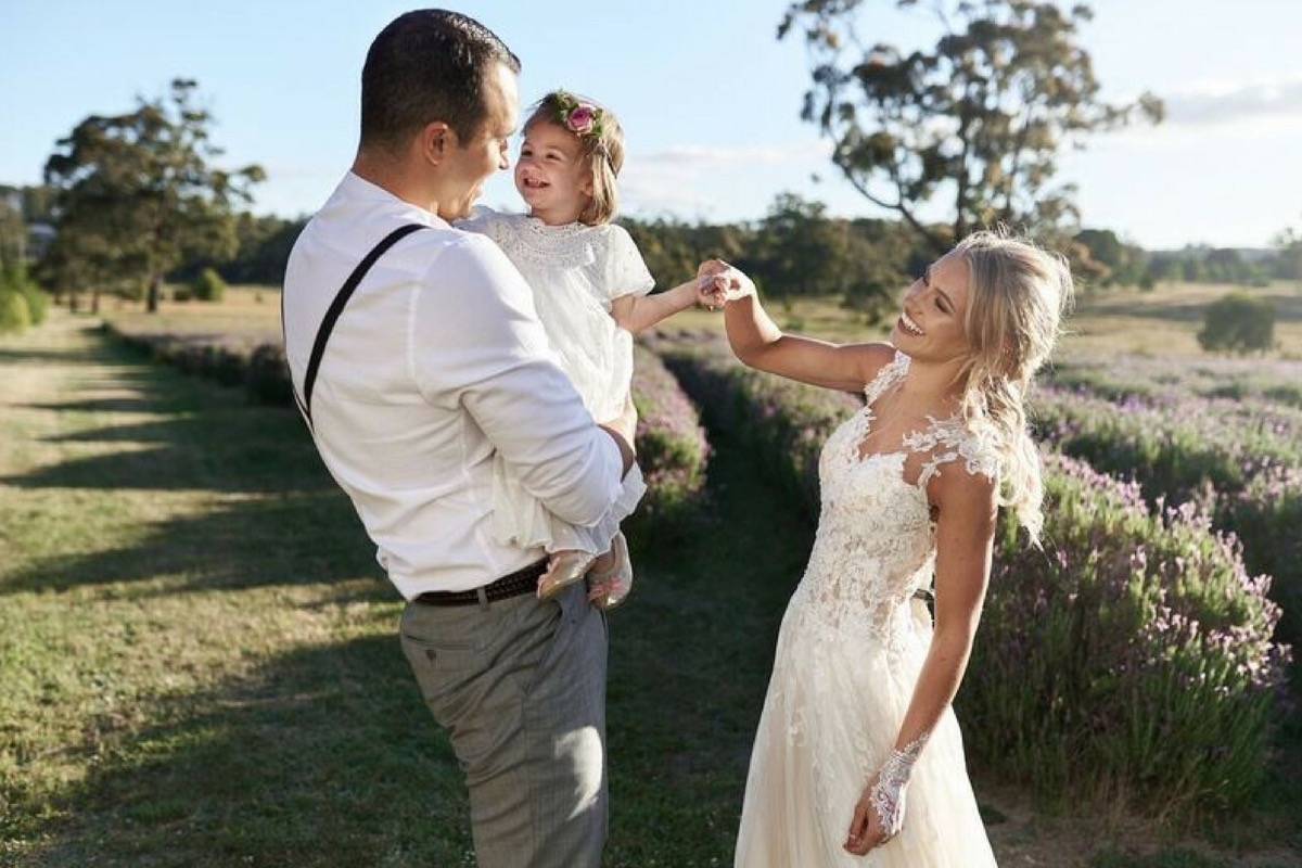 bride_and_groom_with_flower_girl_in_field.jpg