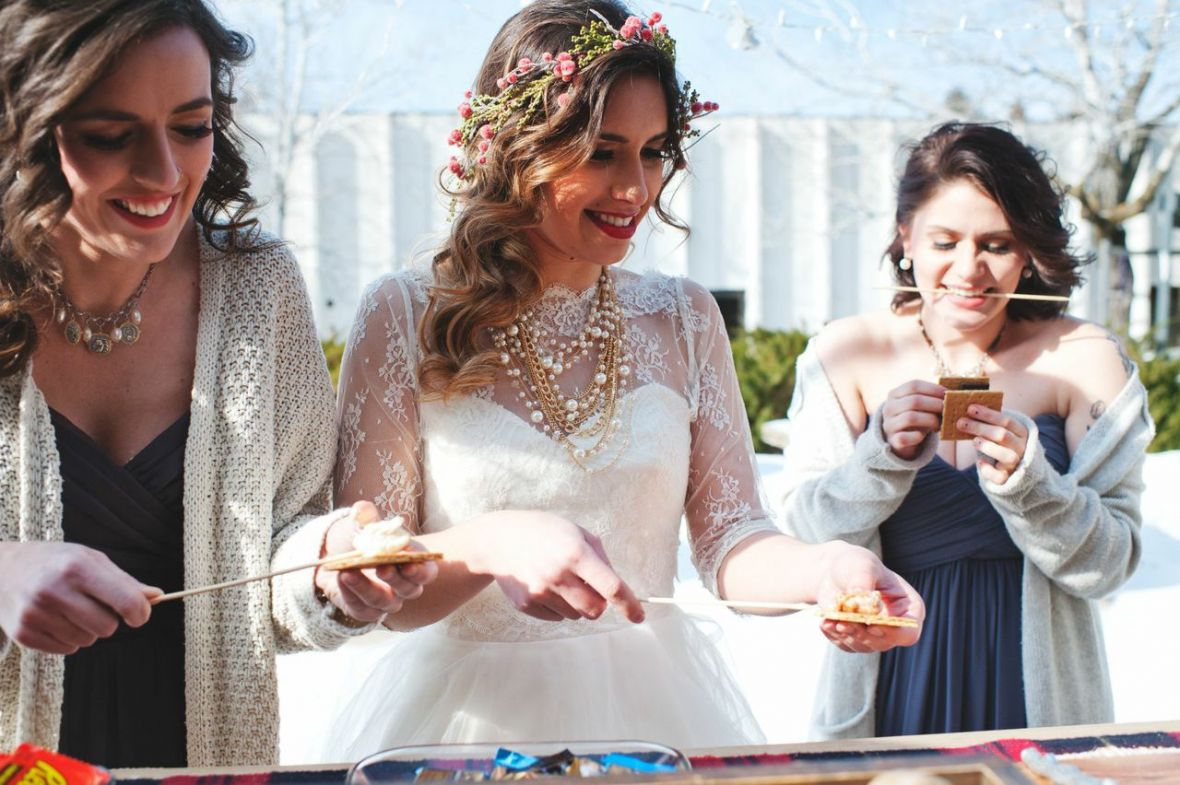 bride_bridesmaids_eating_smores_at_outdoor_smores_bar_winter.jpg