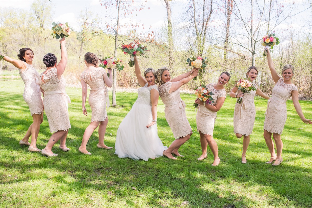 bride_bridesmaids_having_fun_holding_up_bouquets.jpg