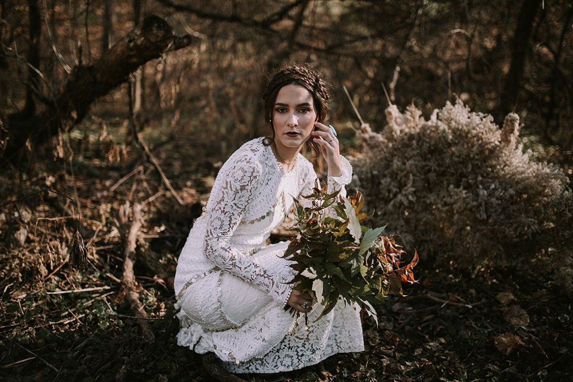 bride_crouching_on_knees_in_forest_wedding_day_serious.jpg
