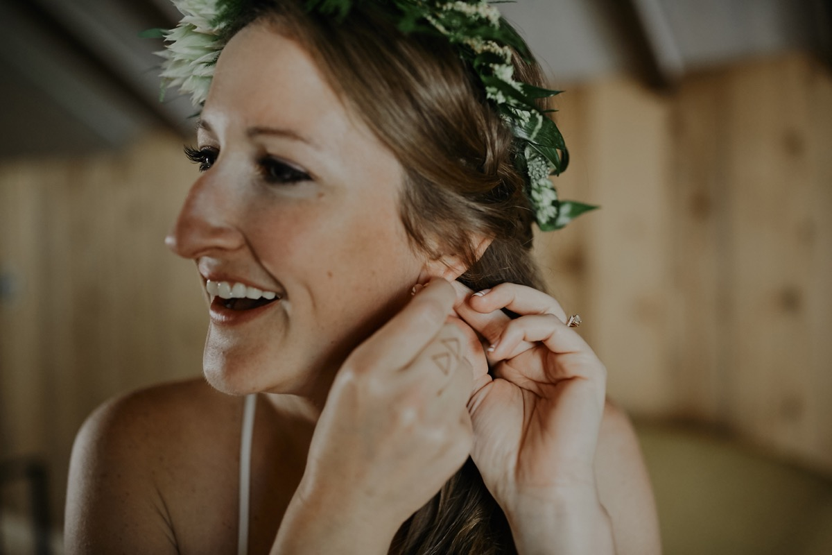 bride_greenery_flower_crown_smiling_putting_in_earrings.JPG