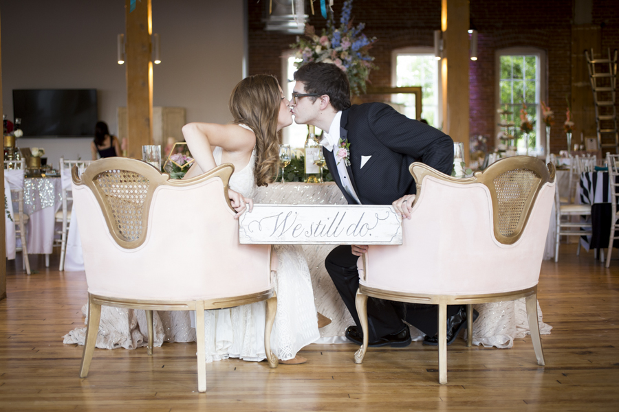 bride_groom_blush_pink_chairs_kissing_we_still_do_wooden_sign.JPG