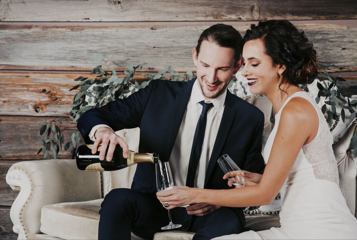 bride_groom_champagne_toast_sitting_white_couch_greenery_rustic_wood_behind.jpg