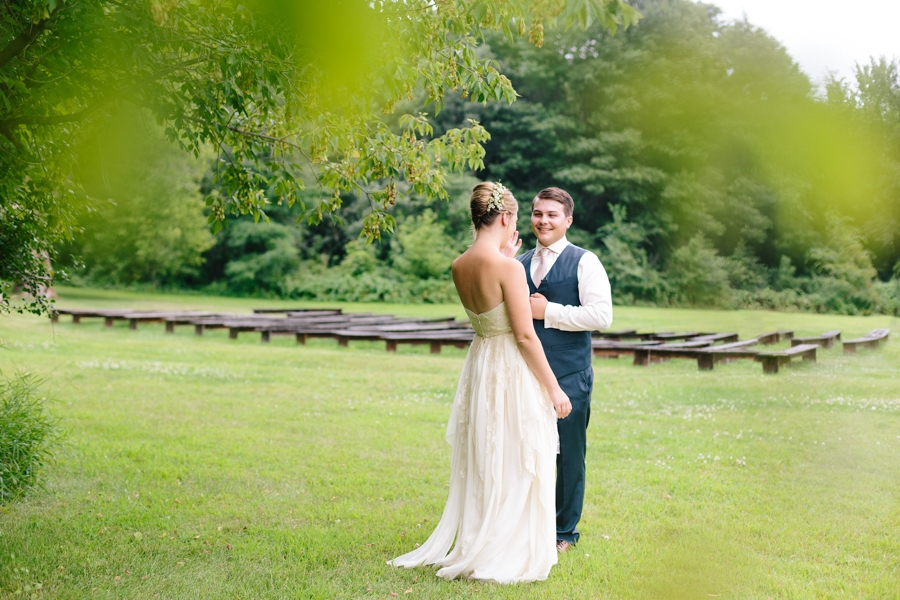 bride_groom_first_look_outdoors_on_grass_around_trees_with_wooden_benches.jpg