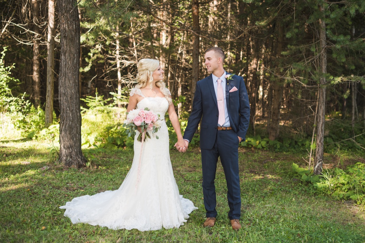 bride_groom_holding_hands_in_forest_fall_wedding_minnesota.jpg
