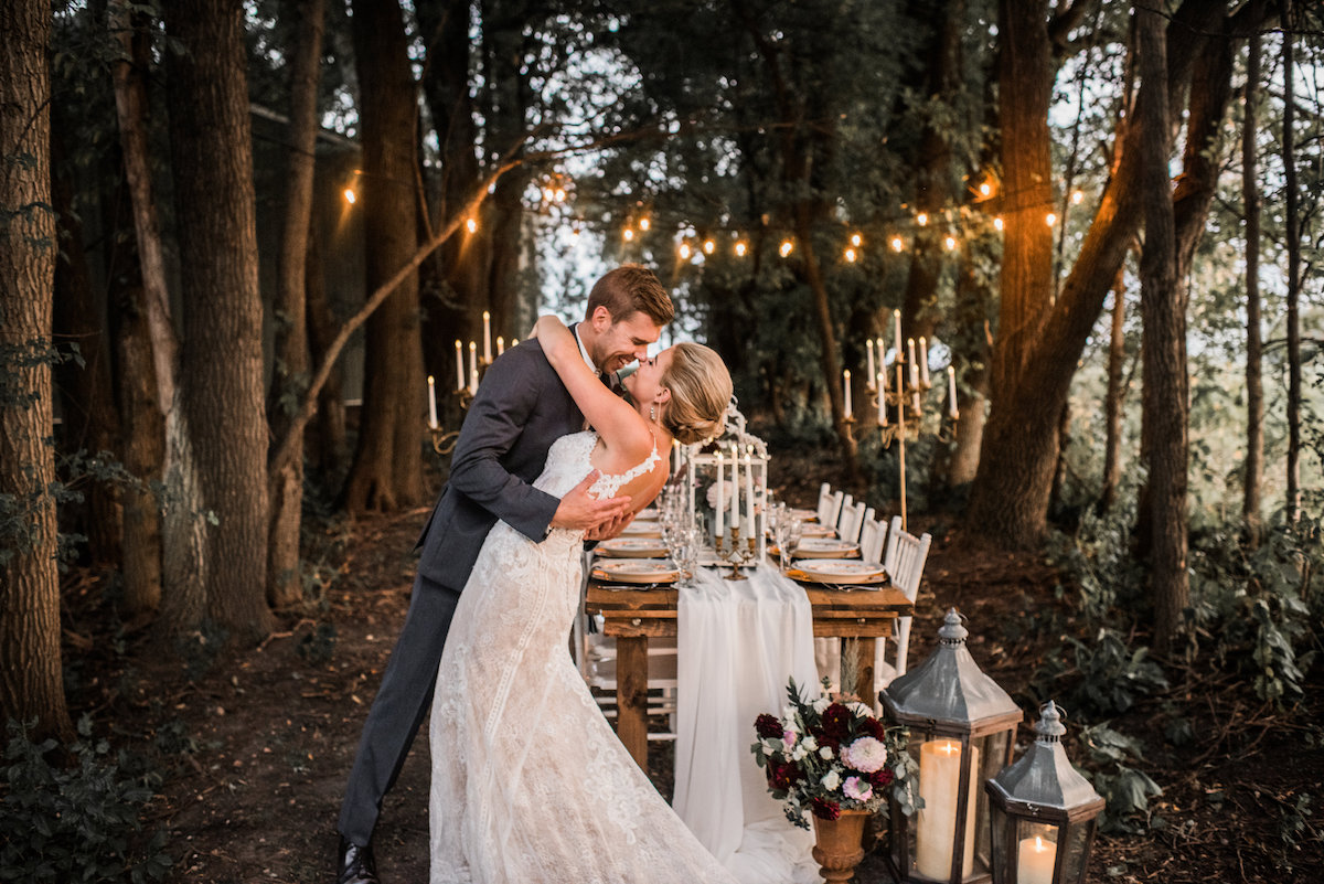 bride_groom_in_woods_with_twinkling_lights_embracing.jpg