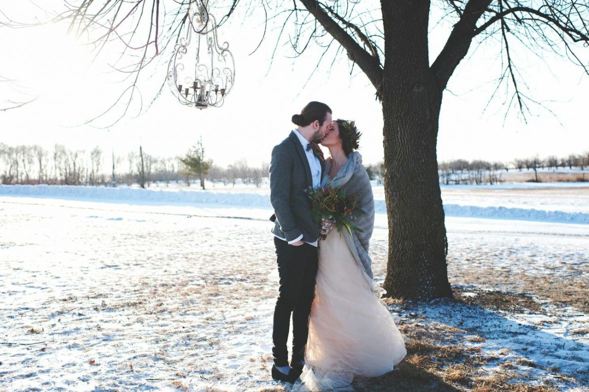 bride_groom_kissing_in_winter_snow_underneath_chandelier_in_tree.jpg