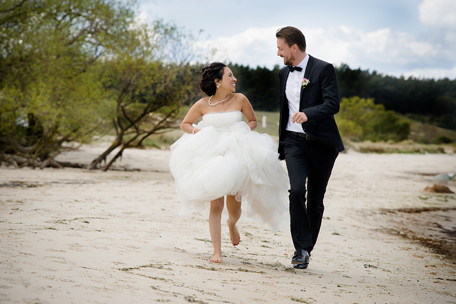 bride_groom_running_barefoot_sand_coastal_wedding.jpg