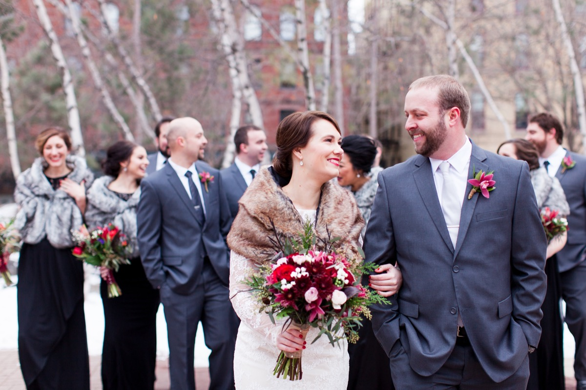 bride_groom_smiling_wedding_party_background_blue_suits_brown_shawl_lace_long_sleeve_dress.jpg