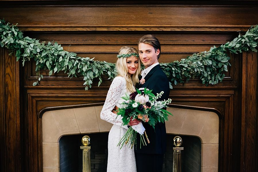 bride_groom_standing_at_cozy_fireplace_with_greenery.jpg