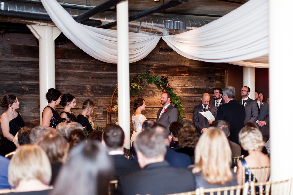 bride_groom_staring_smiling_wooden_walls_arch_white_drapes.jpg