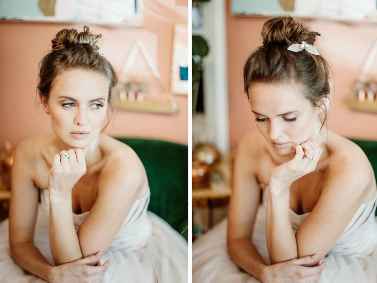 bride_hair_bun_resting_head_on_hand_peach_wall.jpg
