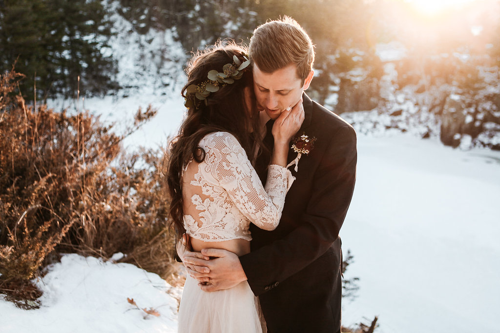 bride_holding_groom_face_in_the_golden_hour_snow.jpg