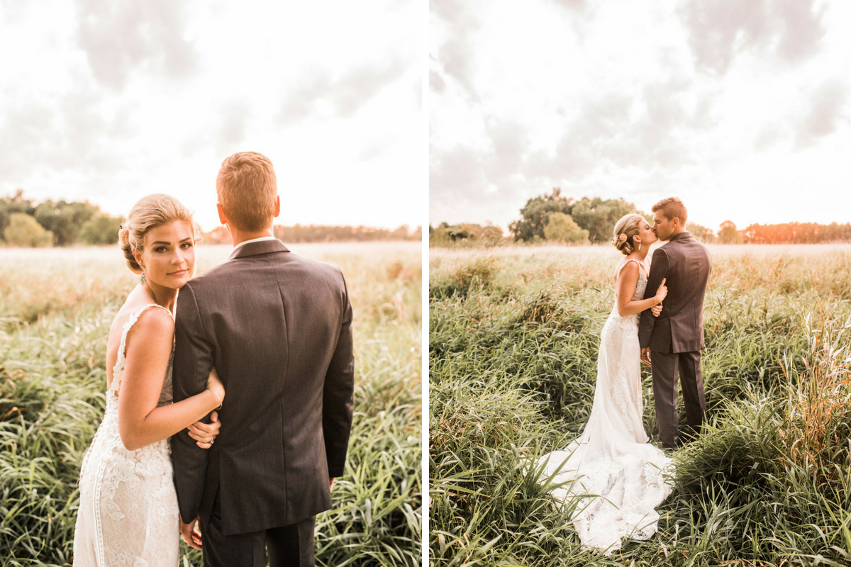 bride_holding_grooms_arm_in_tall_grassy_field_golden_hour_kiss.jpg