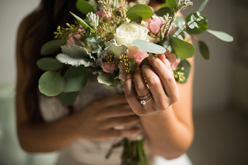 bride_holding_pink_and_yellow_bouquet_with_details_of_engagement_ring_wedding_band.JPG