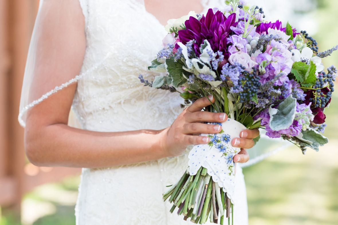 bride_holding_purple_bouquet_white_fabric_wrapped_around_blue_flowers.jpg