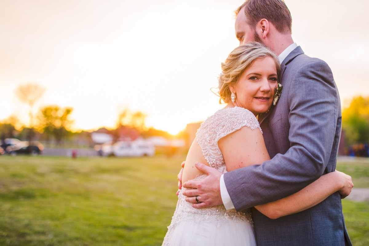bride_hugging_groom_looking_at_camera_sunset_pictures.jpg