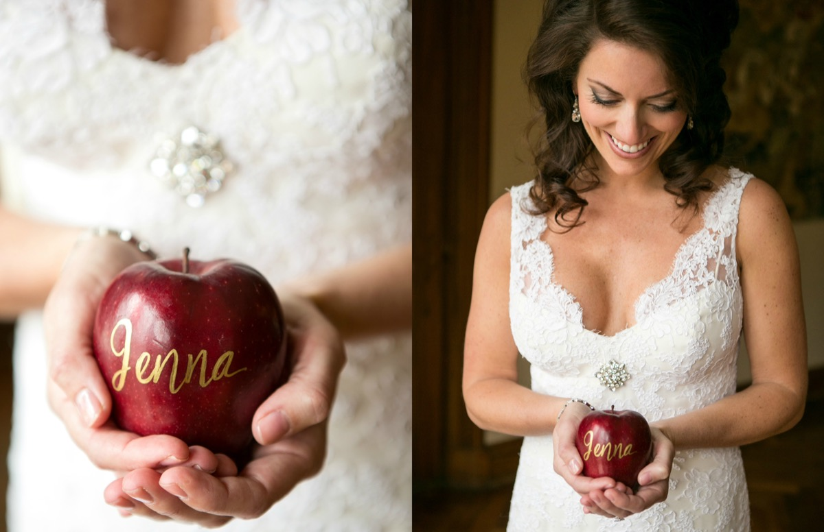 bride_in_lace_gown_holding_real_apple_place_card_handwritten_gold_lettering_guests_names_jenna.jpg