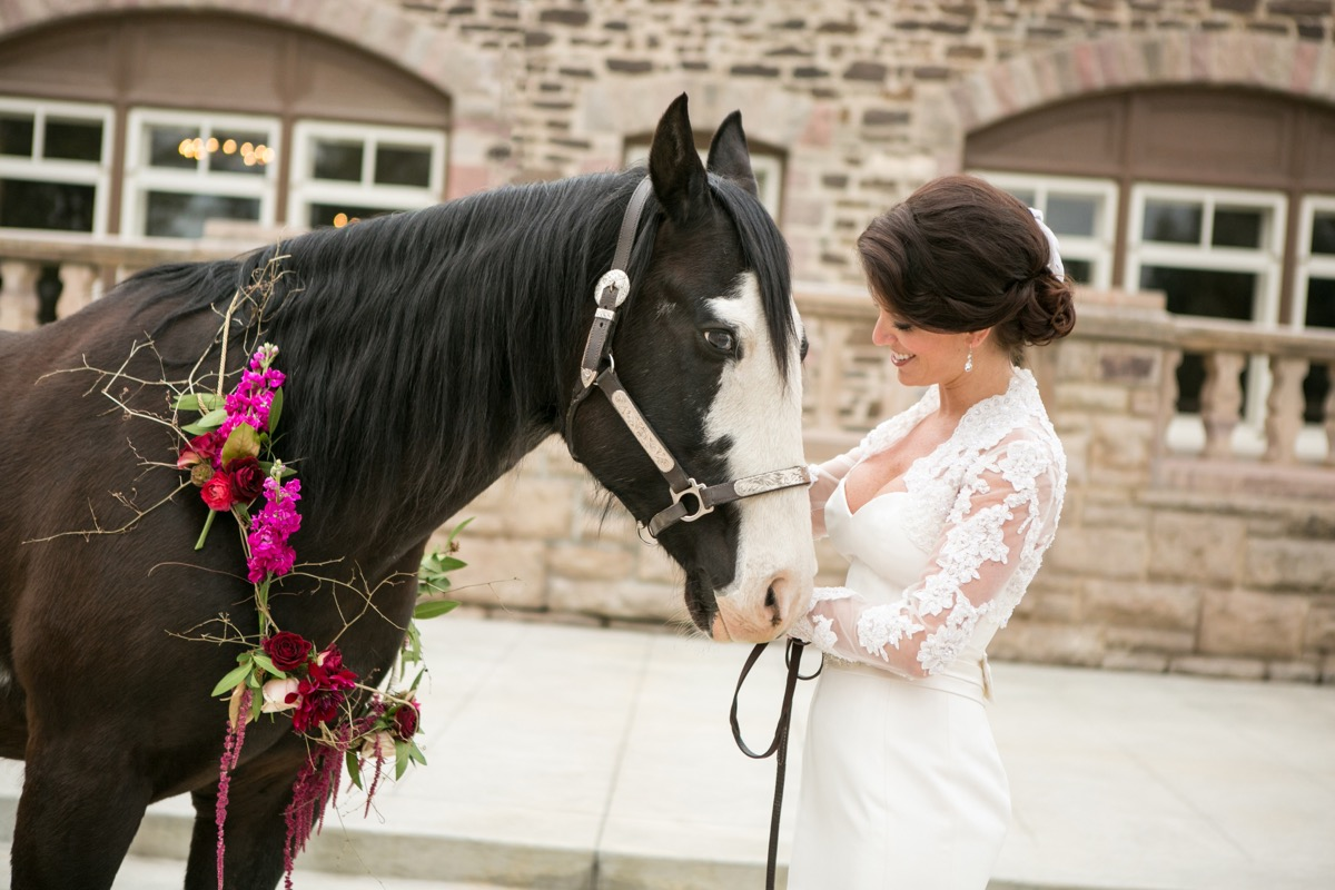 bride_in_simple_lace_long_sleeve_gown_petting_brown_and_white_horse_wrapped_in_pink_red_greenery_flowers.jpg