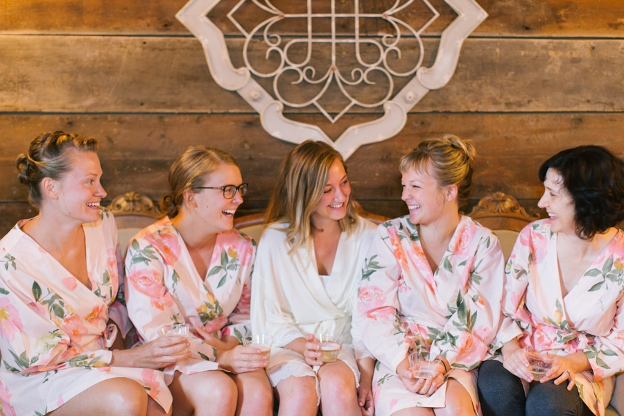 bride_in_white_robe_laughing_with_bridesmaids_in_pink_floral_robes.jpg