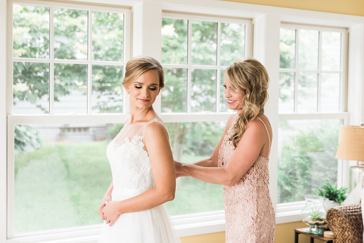 bride_in_yellow_room_bridesmaid_buttoning_up_back.jpg
