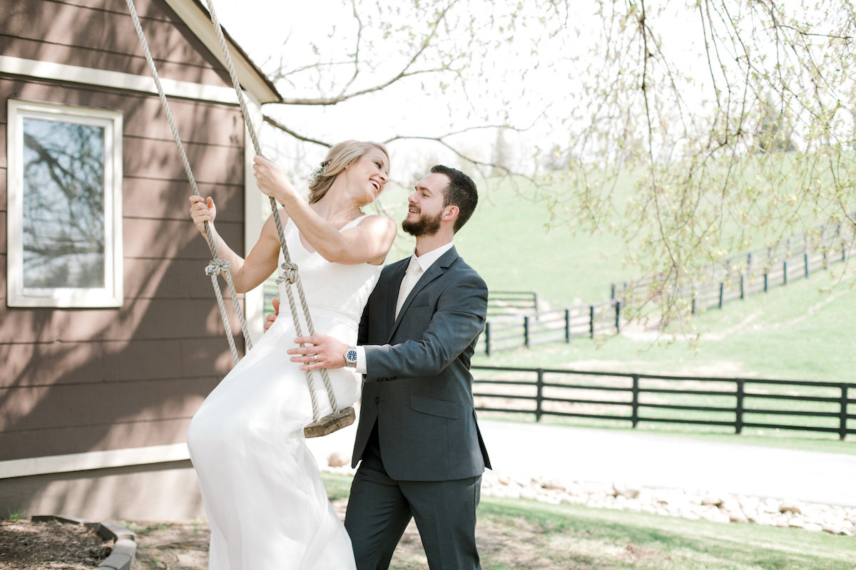 bride_laughing_on_swing_as_groom_pushes_her_smiling.jpg