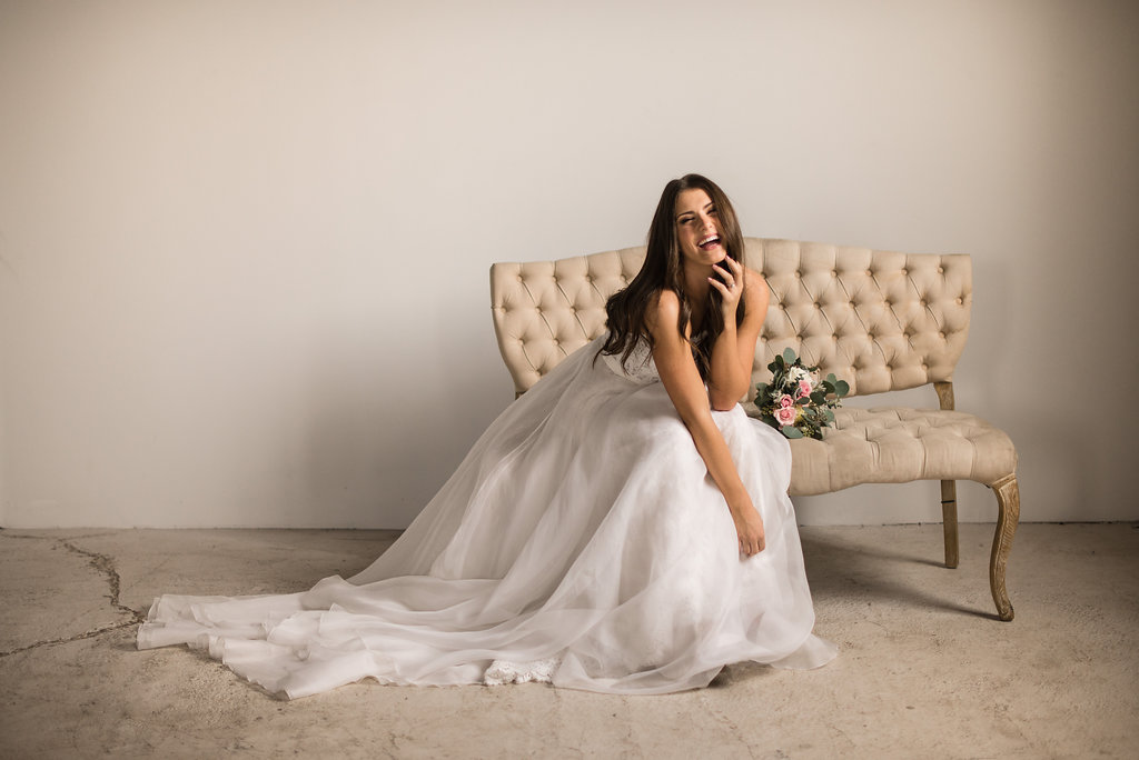 bride_laughing_sitting_on_tan_chair_with_bouquet.JPG