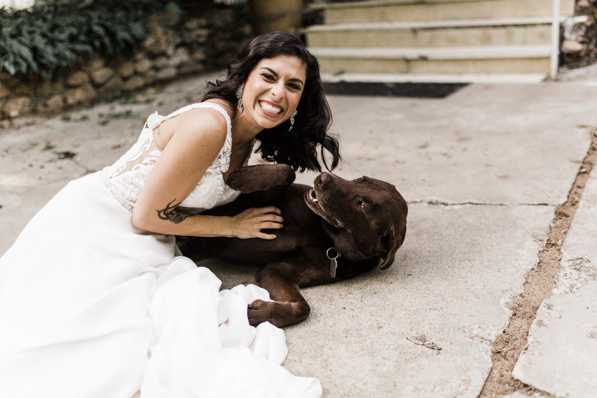 bride_laughing_with_brown_dog_wedding_day.jpg