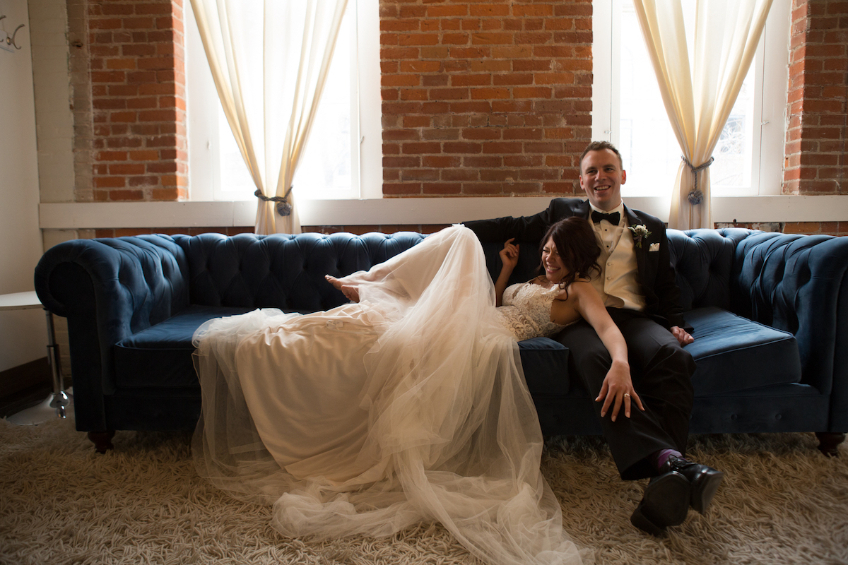 bride_leaning_against_groom_on_navy_felt_couch_against_brick_walls.jpg