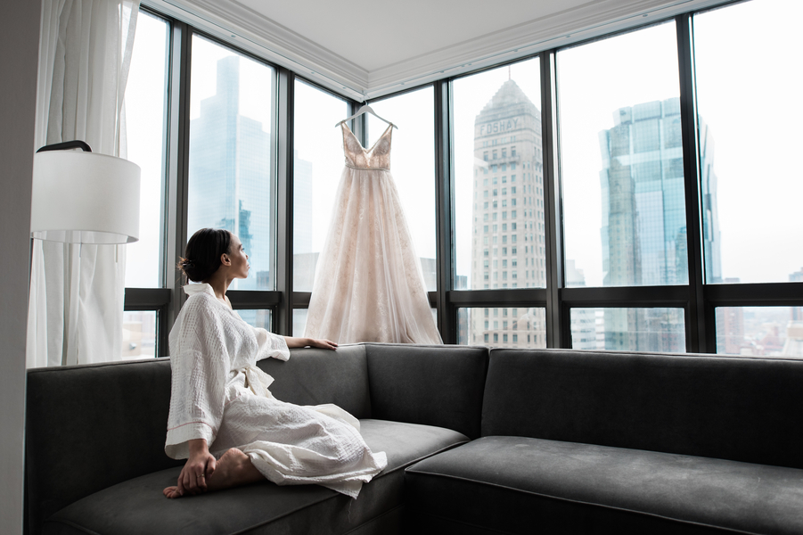 bride_looking_at_wedding_dress_hanging_on_window_with_city_skyline_background.jpg