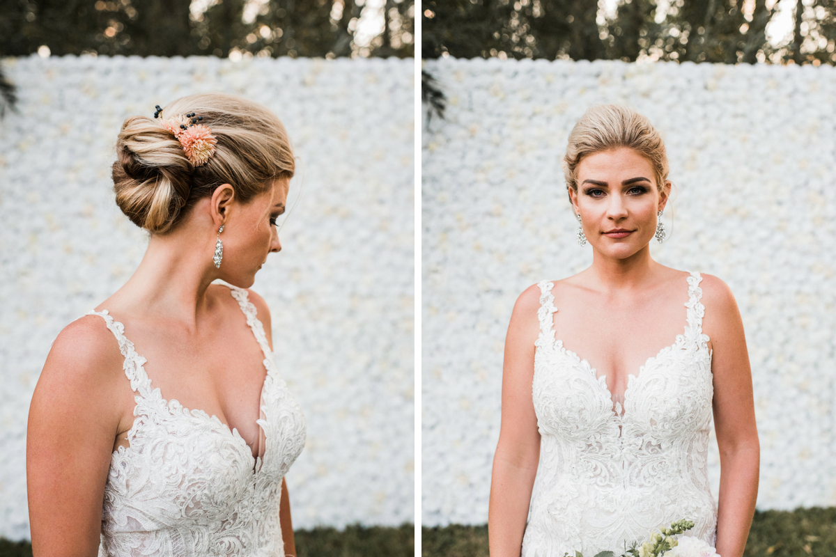 bride_looking_away_in_front_of_white_floral_backdrop_flowers_in_hair_updo.jpg
