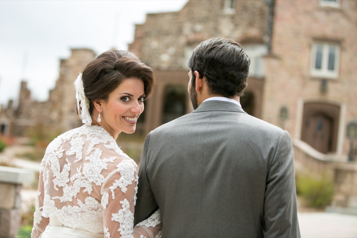 bride_looking_back_smiling_linking_arms_with_groom_in_gray_suit_castle_wedding_inspiration.jpg