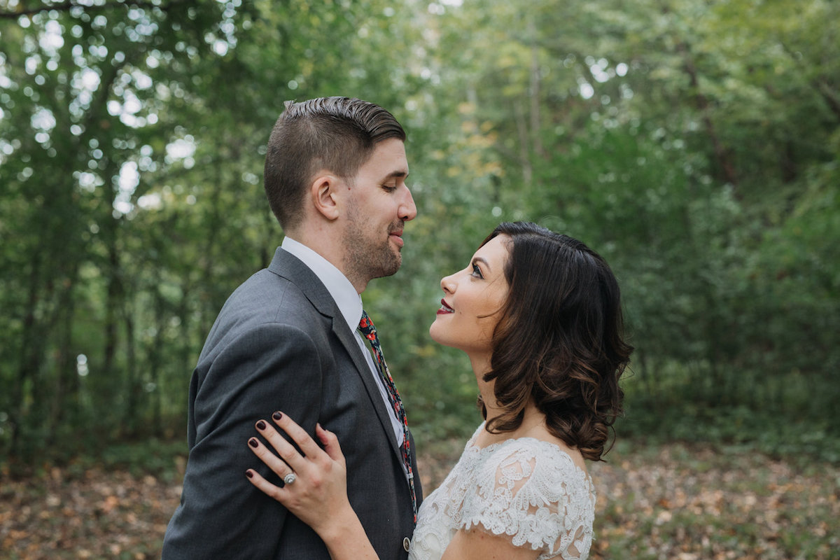 bride_looking_up_smiling_at_groom_in_woods_during_autumn.jpg