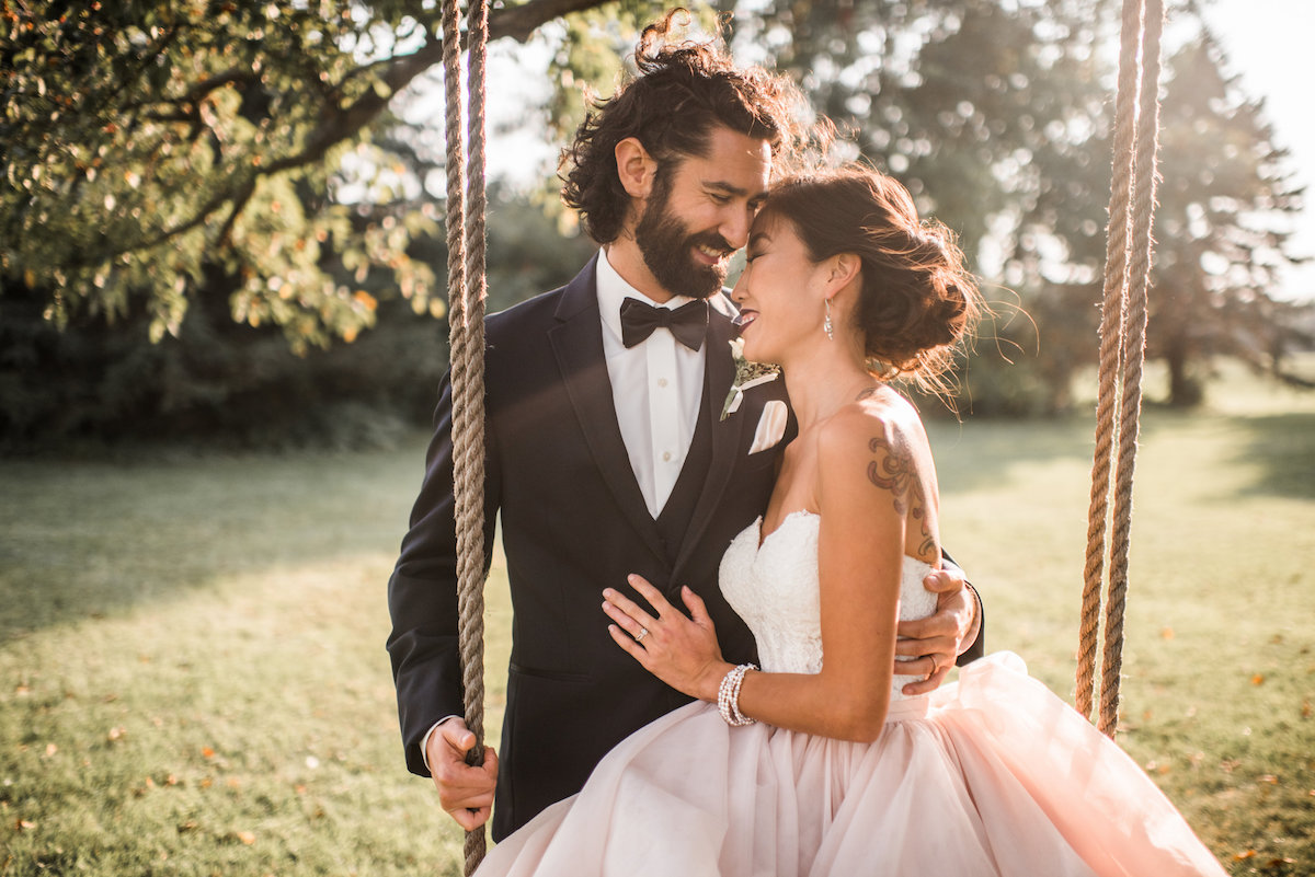 bride_on_swing_laughing_with_groom_at_sunset.jpg