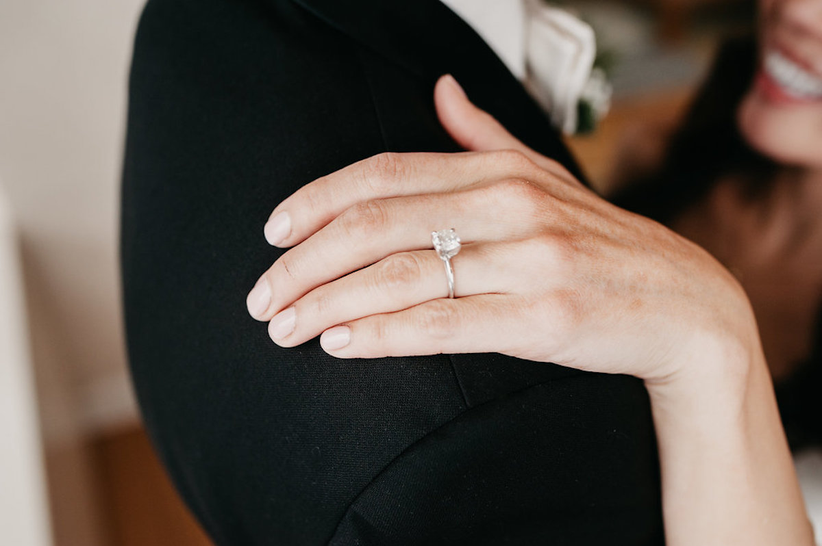 bride_placing_hand_on_grooms_shoulder_silver_wedding_ring.jpg