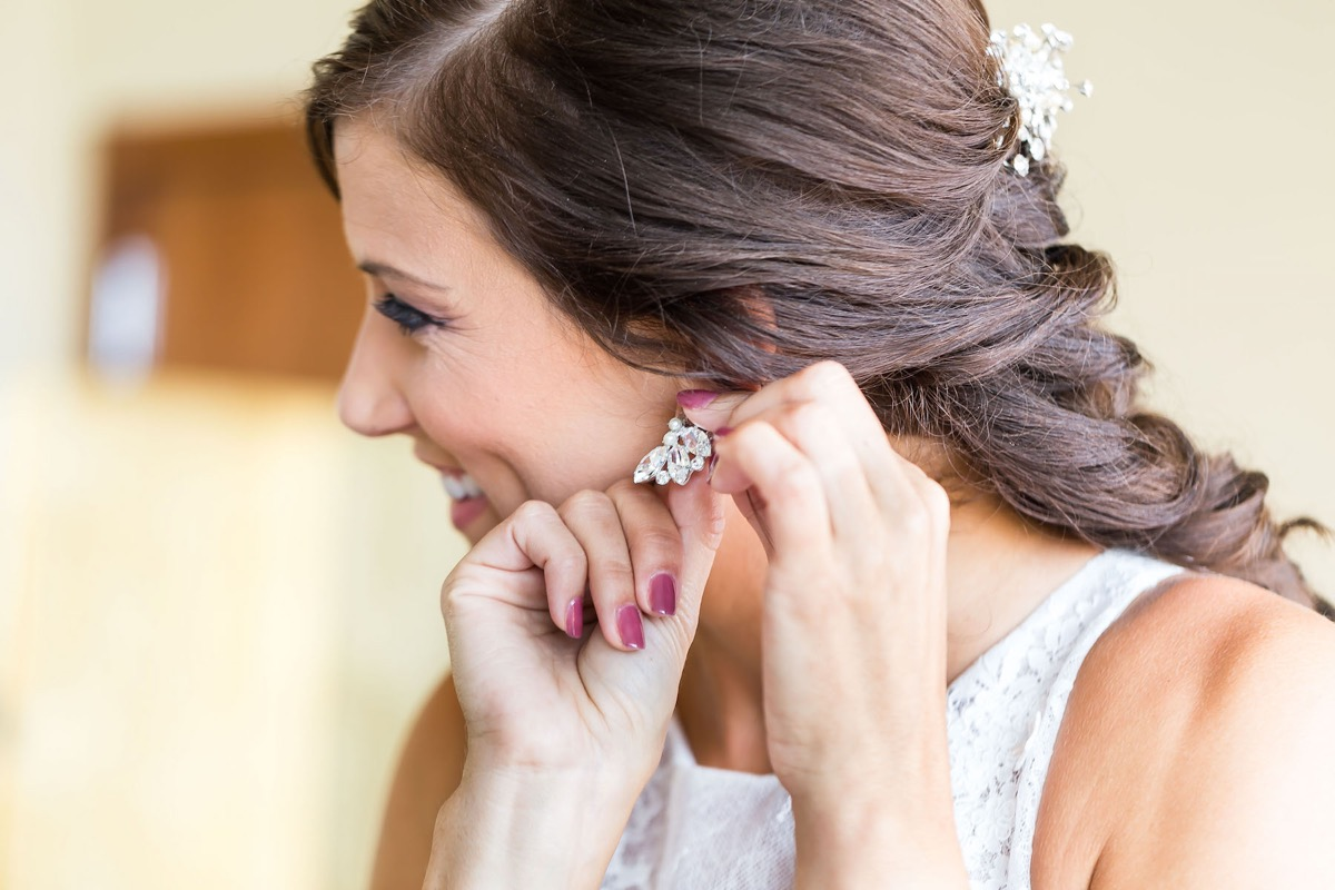 bride_putting_in_white_pearl_drop_down_earrings.jpg