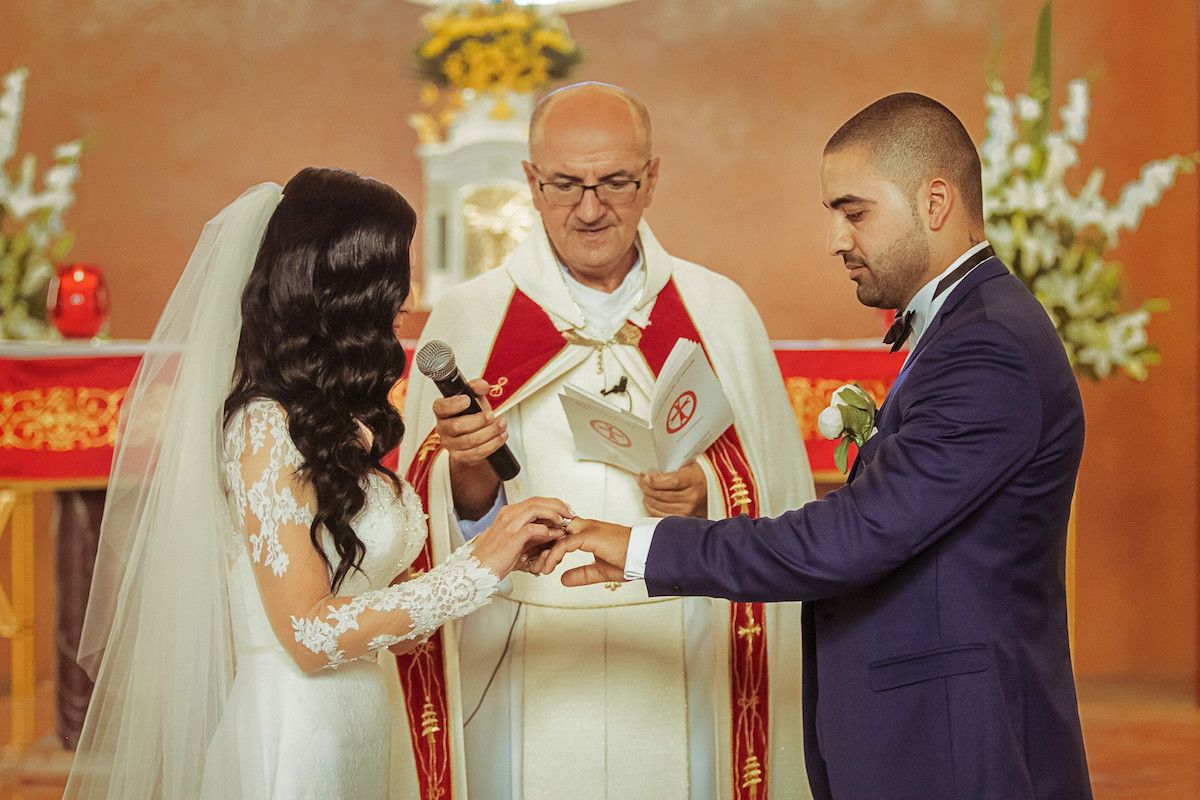 bride_putting_ring_on_grooms_finger_during_wedding_ceremony_in_church.jpg