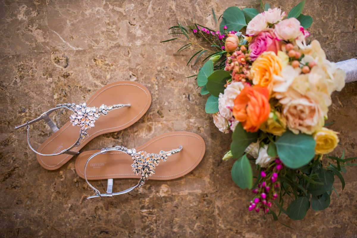 bride_sandals_next_to_bright_bouquet_on_tan_floor.jpg