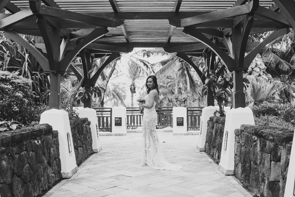 bride_side_angle_standing_under_tropical_structure.jpg
