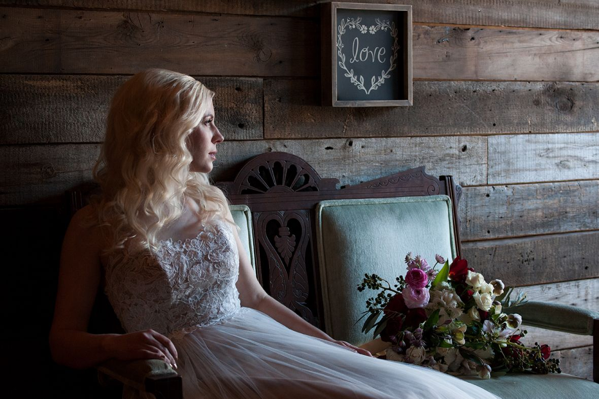 bride_sitting_in_green_cushion_chair_looking_out_window.jpg