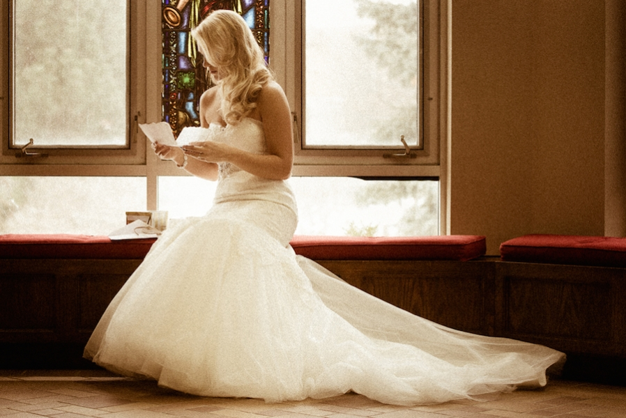 bride_sitting_on_red_cushions_reading_letter.jpg